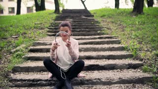 Woman sitting on the stairs in the park and wearing headphones