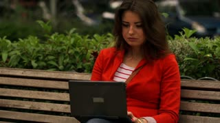 Woman sitting on the street bench and working on laptop, steadycam shot