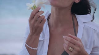 Woman smelling flower on the beach, steadycam shot