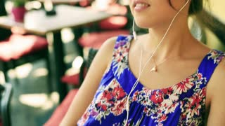 Woman smiling to the camera and listening music on earphones in the street cafe