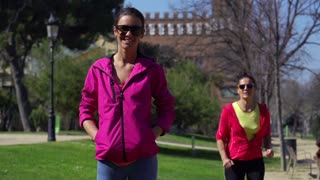 Woman smiling to the camera in park, slow motion shot at 240fps, steadycam shot