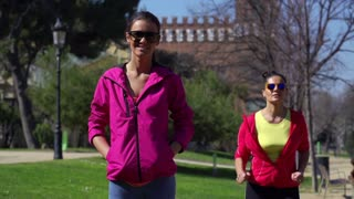 Woman smiling to the camera in park, slow motion shot at 60fps, steadycam shot