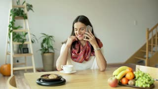 Woman smiling to the camera while drinking coffee and talking on cellphone