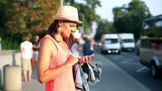 woman standing at the bus stop and using a cellphone