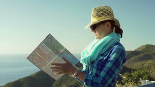 Woman standing on the hill and looking on the map, steadycam shot