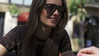 Woman talking and drinking beverage on street cafe, steadycam shot