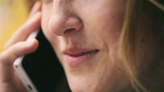 Woman talking on cellphone and smiling, closeup