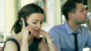 Woman talking on cellphone in the cafe next to her boyfriend