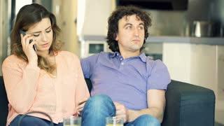 Woman talking on cellphone while sitting next to her boyfriend, steadycam shot