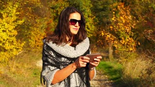 Woman texting on smartphone in the autumnal scenery, steadycam shot