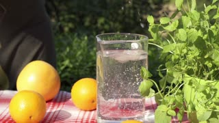 woman throwing ice cubes into the jug of water, slow motion shot at 240fps