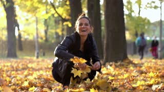 Woman throwing leaves in the air and smiling to the camera, slow motion shot