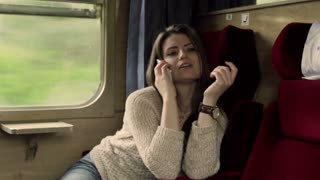 Woman traveling by train and talking on cellphone, steadycam shot