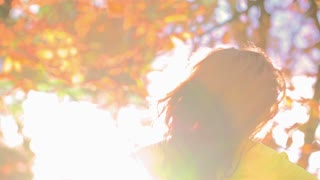 Woman twisting around in sunlight, slow motion shot at 240fps, steadycam shot