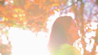 Woman twisting around in sunlight, slow motion shot, steadycam shot