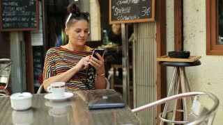 woman typing on the cellphone and sitting by the table outside the cafe