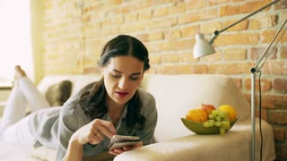 Woman using smartphone and lying on the sofa