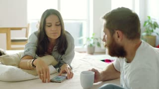 Woman using smartphone and talking to her boyfriend who is drinking coffee