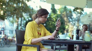Woman using smartphone as a mirror while powdering face and drinking coffee