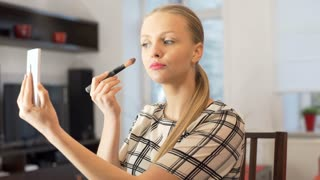 Woman using smartphone as a mirror while powdering her face