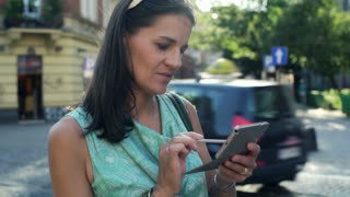 Woman using smartphone in the city and smiling to the camera, steadycam shot