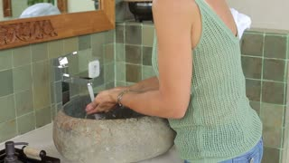 Woman using soap and cleaning her hands in the bahtroom