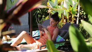 Woman using tablet and lying on sunbed