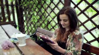 Woman using tablet in the arbour and smiling to the camera