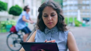 Woman using tablet in the street cafe and smiling to the camera