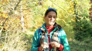 Woman walking in the autumnal forest and drinking water, steadycam shot