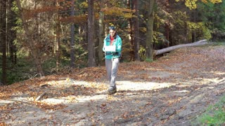 Woman walking in the autumnal forest and reading a map