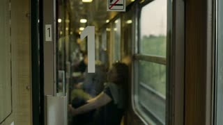 Woman walking in the train and enter compartment, steadycam shot