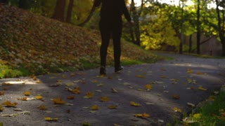 Woman walking on path in the autumnal park, slow motion shot