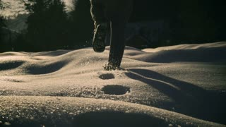 Woman walking on snow and leaving tracks, steady, slow motion shot at 240fps