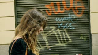 Woman walking on the street with graffiti on the walls, steadycam shot