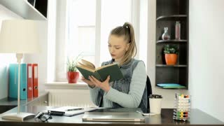 Woman walking to the window while reading book in the office, steadycam shot