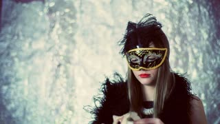 Woman wearing black, carnival mask and looking thoughtful