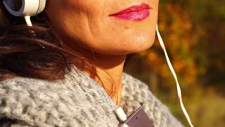 Woman wearing headphones and listening music, steadycam shot, slow motion shot a