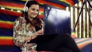 Woman wearing headphones and using laptop on the swing