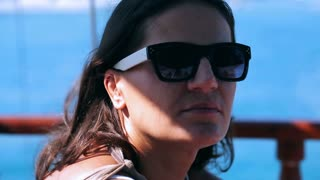 Woman wearing sunglasses and enjoying time on windy day