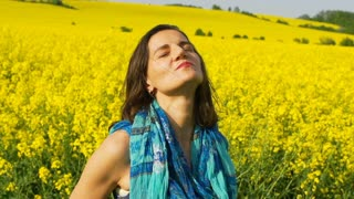 Woman with eyes shut relaxing on the field, steadycam shot, slow motion shot at