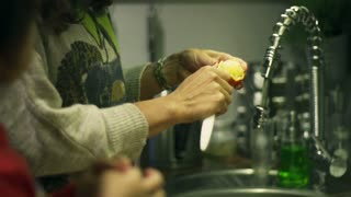 Woman with son peeling orange in the kitche, steadycam shot