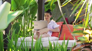 Woman working on laptop in exotic place