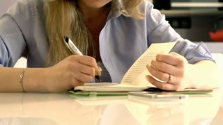 Woman writing something in her journal and smiles to the camera, steadycam shot