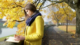 Woman writing something in notebook in the autumnal park