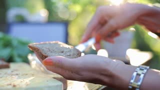 woman's hands applying white cheese on a slice of bread