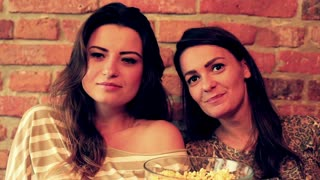 Women eating popcorn and smiling to the camera