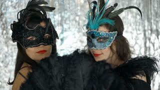 Women in carnival masks smiling to the camera at the party, steadycam shot