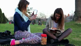 Women sitting in park using tablet reading book and talking.