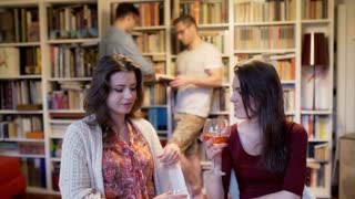 Women smiling to the camera and men looking at books at the party